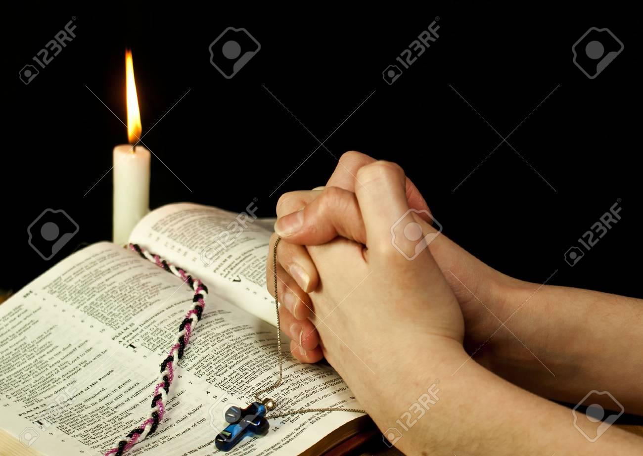 9035001-bible-ouverte-avec-combustion-bougie-et-les-mains-de-prière-femme