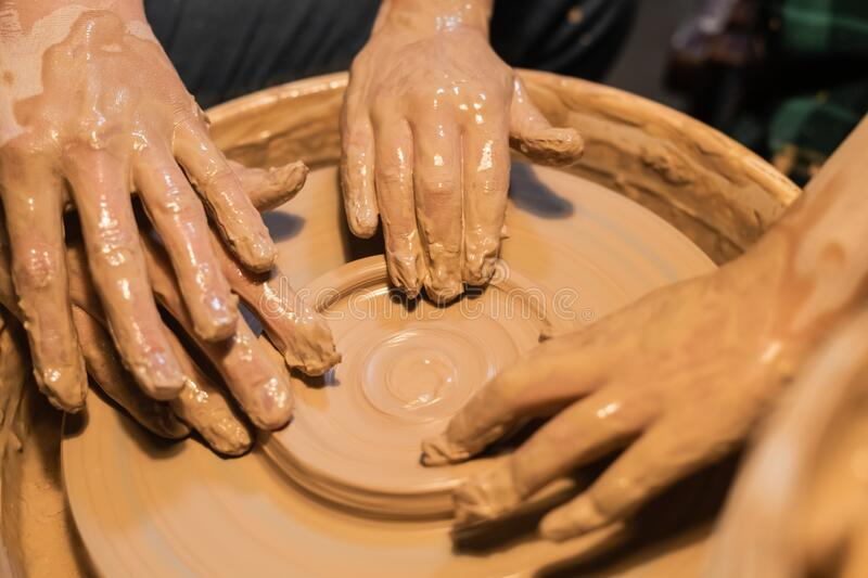 gros-plan-des-mains-d-une-femme-et-un-enfant-en-argile-dans-atelier-de-poterie-194691787